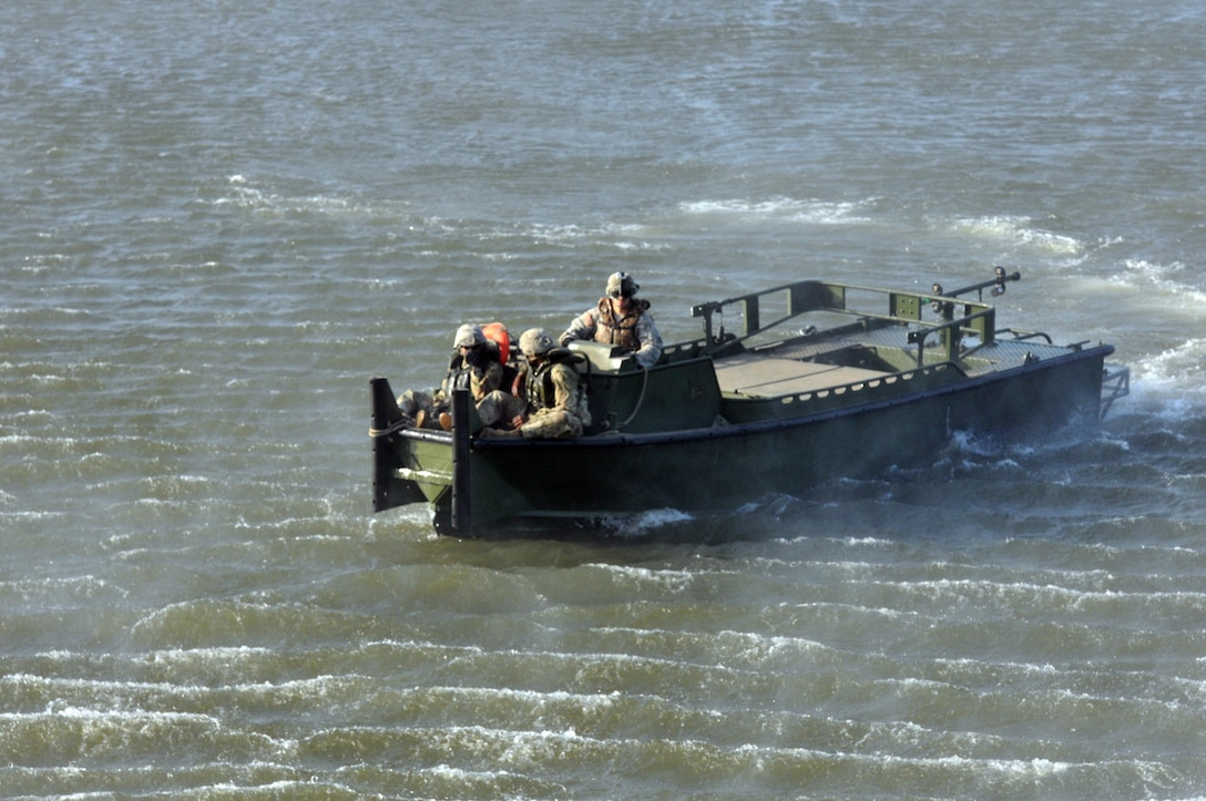 Three U.S. Army Soldiers from a Multi-Role Bridge Company in a MKII Bridge Erection Boat retrieve an Improved Ribbon Bridge (IRB) Bay Section that was dropped off by a CH-47 Chinook of Company B, 7th (General Support Aviation) Battalion, 158th Aviation Regiment, 244th Aviation Brigade, Army Reserve Aviation Command during River Assault 2017 on Fort Chaffee Manuever Training Center, July 26, 2017. The Bay was among several that formed a IRB across the river, the culminating event of River Assault. Operation River Assault, July 26, 2017. Operation River Assault is one of the key training events that demonstrates that America's Army Reserve is the most capable, combat ready, and lethal Federal Reserve Force in the history of the nation. (U.S. Army Reserve Photo by Sgt. 1st Class Clinton Wood)