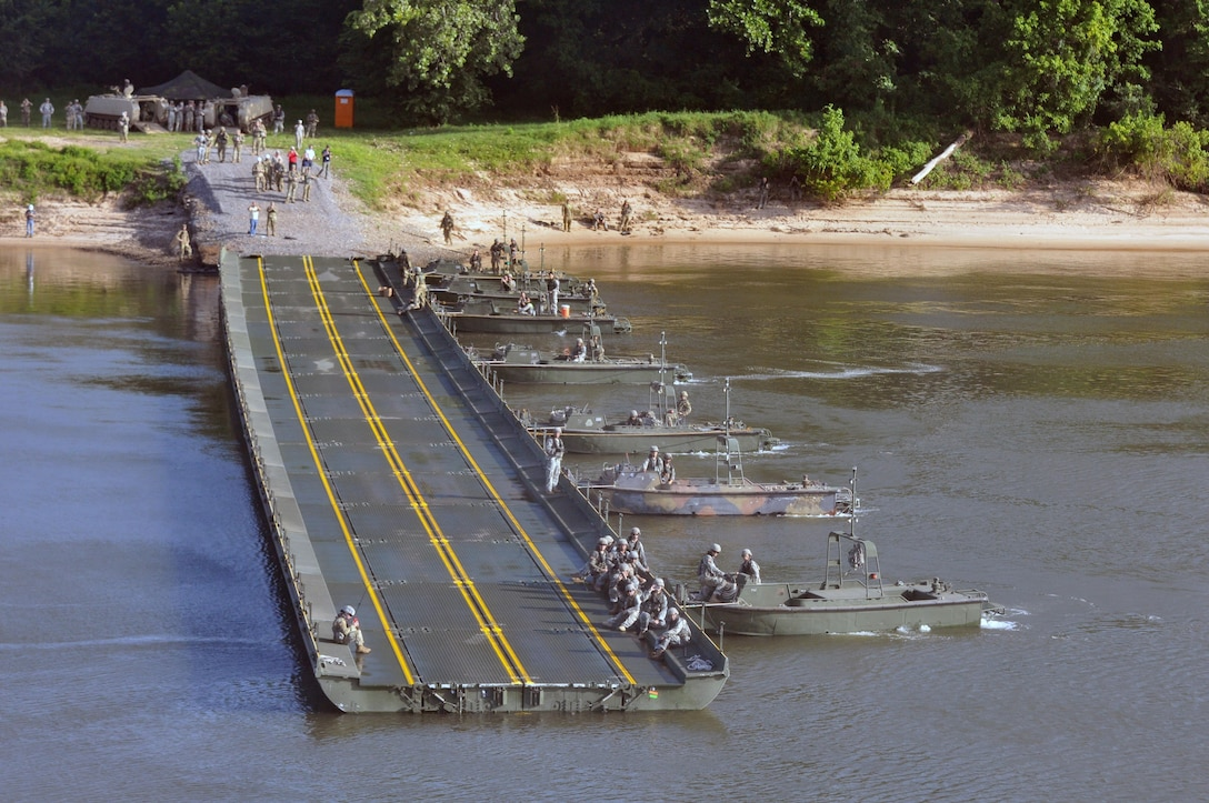 MKII Bridge Erection Boats position against the current Improved Ribbon Bridge (IRB) Bay Sections across the  Arkansas River during River Assault 2017 on Fort Chaffee Manuever Training Center, July 26, 2017. The estimated 300-meter IRB across the river was the culminating event of River Assault. The two M113 Armored Personnel Carriers on the shore were the first two vehicles to drive on the completed bridge. Operation River Assault is one of the key training events that demonstrates that America's Army Reserve is the most capable, combat ready, and lethal Federal Reserve Force in the history of the nation. (U.S. Army Reserve Photo by Sgt. 1st Class Clinton Wood)