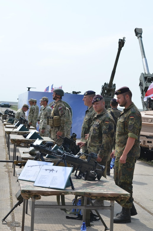 From right, German, Slovenian and Georgian troops man tables displaying their countries' weapons during the opening ceremonies for exercise Noble Partner at Vaziani Military Base, Georgia, July 30, 2017. Army photo by Sgt. Shiloh Capers
