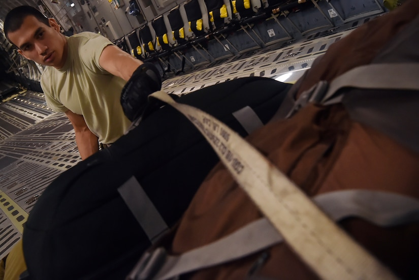 Senior Airman Raymond Salas, 15th Airlift Squadron C-17 Globemaster III loadmaster, secures luggage and cargo here, prior to departing for Joint Base Lewis-McChord, Washington State, in support of Exercise Mobility Guardian July 31. Mobility Guardian is designed to enhance the capabilities of mobility Airmen to succeed in dynamic threat environments. The exercise features more than 3,000 participants and involves 25 countries from July 31 to Aug. 11. (U.S. Air Force photo by Staff Sgt. Christopher Hubenthal)