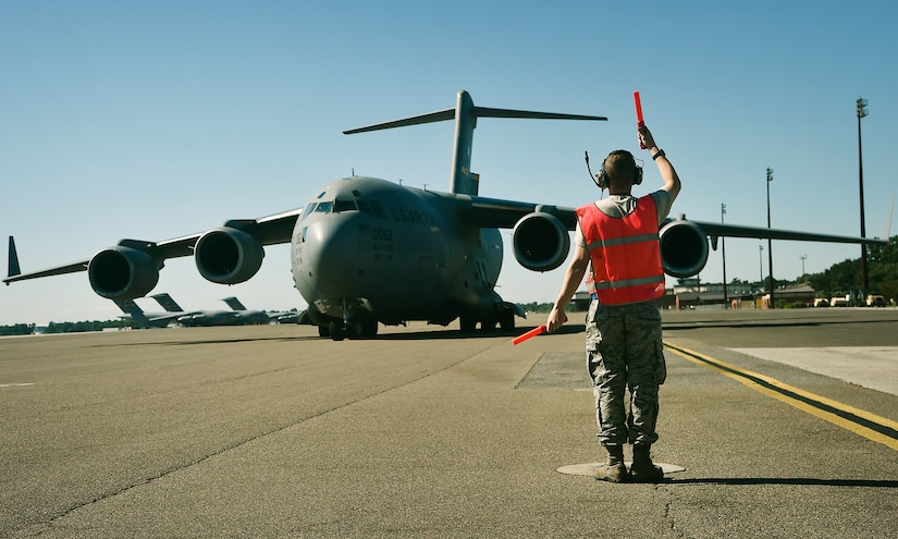 Airman 1st Class David Jackson, 437th Aircraft Maintenance Squadron, marshals out a C-17 Globemaster III here, as it prepares to depart to Joint Base Lewis-McChord, Washington State, in support of Exercise Mobility Guardian July 31. Mobility Guardian is designed to enhance the capabilities of mobility Airmen to succeed in dynamic threat environments. The exercise features more than 3,000 participants and involves 25 countries from July 31 to Aug. 11. (U.S. Air Force photo by Staff Sgt. Christopher Hubenthal)