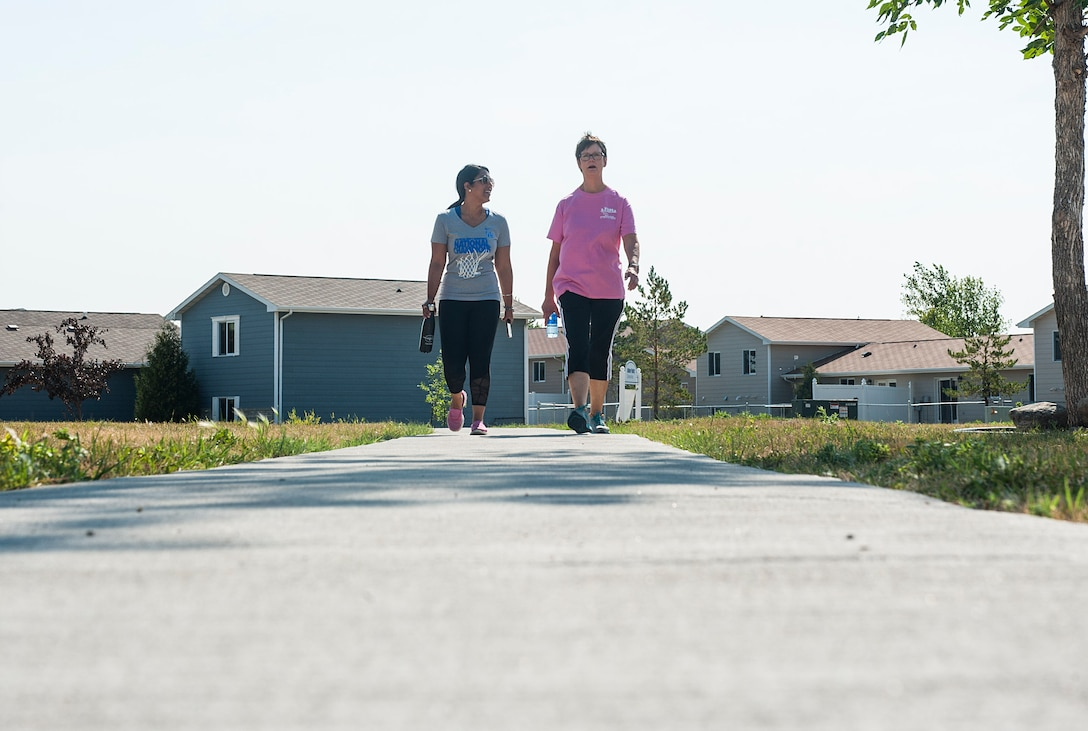 From left, Sheena Swanner, 5th Medical Operations Squadron health promotion dietician, and Lori Halvorson, 5 MDOS health promotion coordinator, walk through Frog Park at Minot Air Force Base, N.D., July 23, 2017. The Minot Monday Community Walks last from 45 minutes to an hour and are used to promote health and wellness in the base community. (U.S. Air Force photo by Airman 1st Class Jonathan McElderry)