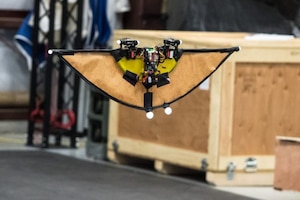 The future hybrid unmanned aerial vehicle is less than a foot in length, but for testing, its inventor has added a lightweight paper wing to slow it down. Army photo by David McNally