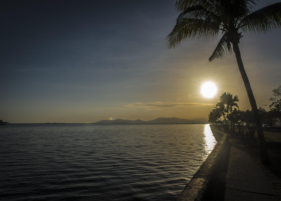 The sun rises over the horizon as waves lap the concrete barrier in the park in front of the Pacific Angel (PACANGEL) 17-3 hotel in Lautoka, Fiji, July 23, 2017. PACANGEL 17-3 built partnerships between the U.S., Fiji, and five regional nations including Australia, Vanuatu, Indonesia, the Philippines and France by conducting multilateral humanitarian assistance and civil military operations, promoting regional military-civilian-nongovernmental organization cooperation and interoperability. (U.S. Air Force photo/Tech. Sgt. Benjamin W. Stratton)