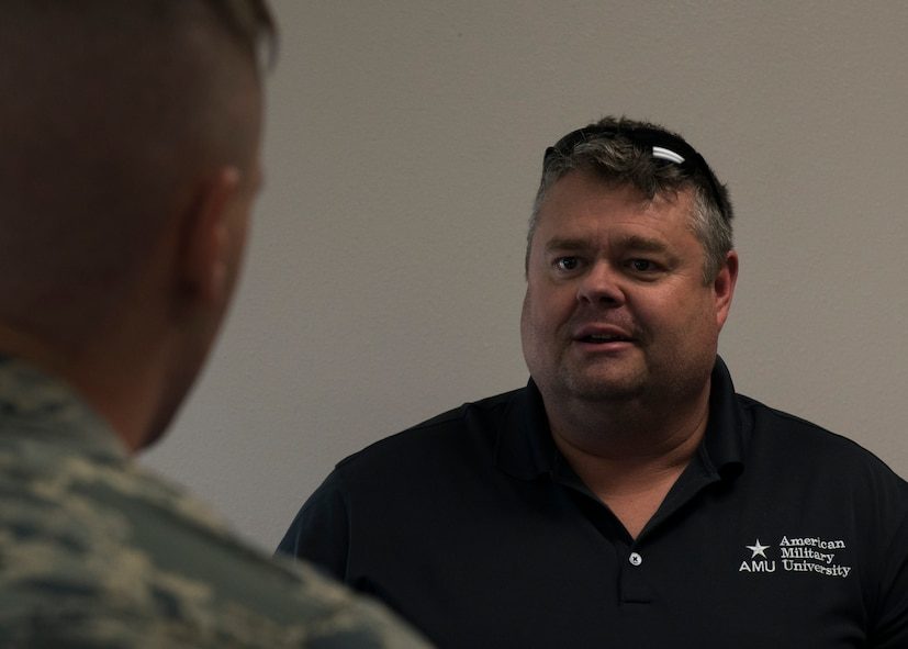 Earl Edwards, American Military University education coordinator, speaks to an Airman at the education fair at Minot Air Force Base, N.D., July 26, 2017. Many universities offer courses for Airmen to complete their Community College of the Air Force degree. (U.S. Air Force photo by Airman 1st Class Alyssa M. Akers)
