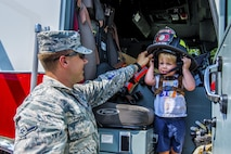 Airman Basic Bryce Postle, 445th Airlift Wing journeyman firefighter, helps hold a firefighter helmet for a toddler during Big Truck Day, July 28, Destin, Fla. Fire, construction, garbage and utility trucks were on display for kids to see up close at the city's annual event. (U.S. Air Force photo/Kristin Stewart)