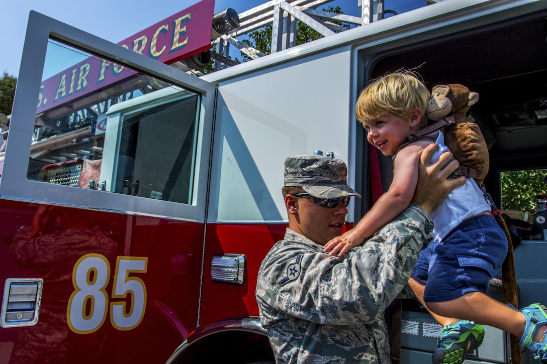 Airman Basic Bryce Postle, 445th Airlift Wing journeyman firefighter, helps a toddler out of a fire engine during Big Truck Day, July 28, Destin, Fla. A 96th Civil Engineer Group fire engine was on display and firefighters educated the community about fire safety. Fire, construction, garbage and utility trucks were on display for kids to see up close at the city's annual event. (U.S. Air Force photo/Kristin Stewart)