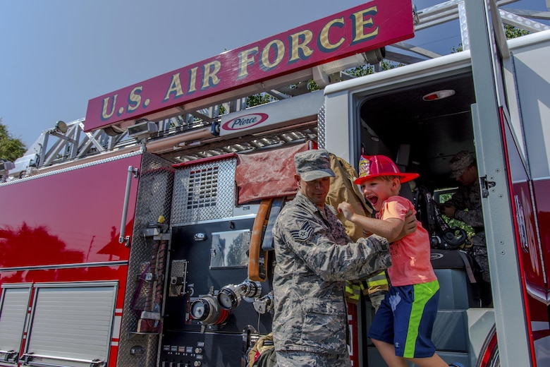 Staff Sgt. Nick Behr, 445th Airlift Wing crew chief, helps a young boy down from a fire engine during Big Truck Day, July 28, Destin, Fla. A 96th Civil Engineer Group fire engine was on display and firefighters educated the public on fire safety. Fire, construction, garbage and utility trucks were on display for kids to see up close at the city's annual event. (U.S. Air Force photo/Kristin Stewart)