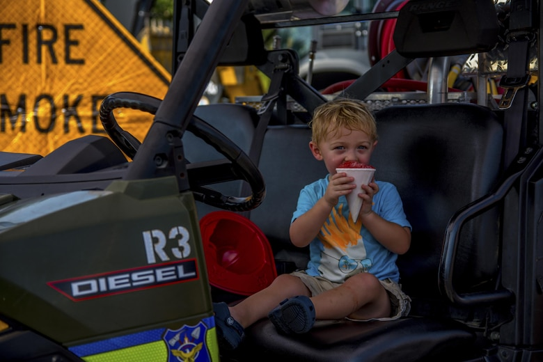 A young boy eats a snow cone while sitting in a Jackson Guard water ranger vehicle during Big Truck Day, July 28, Destin, Fla. Jackson Guard displayed their forestry vehicles and educated event goers about their use during prescribed burns. Fire, construction, garbage and utility trucks were on display for kids to see up close during the city's annual event. (U.S. Air Force photo/Kristin Stewart)