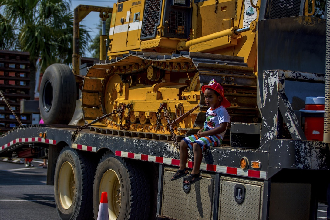 A young boy sits next to a Jackson Guard bulldozer, used to clear debris for prescribed fires, during Big Truck Day July 28, Destin, Fla. Jackson Guard forestry management personnel educated the community about the benefits of prescribed burns. Fire, construction, garbage and utility trucks were on display for kids to see up close at the city's annual event. (U.S. Air Force photo/Kristin Stewart)