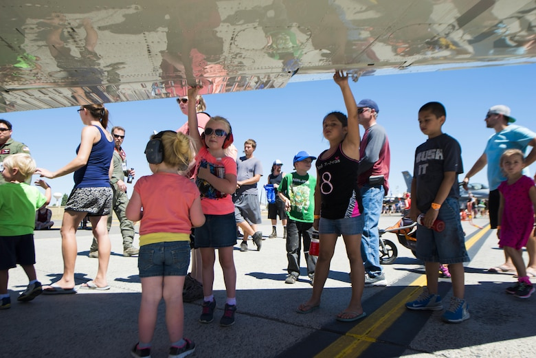 Members from the local and regional community touch the wing of a static display aircraft during SkyFest 2017 Air Show and Open House at Fairchild Air Force Base, Washington, July 30, 2017. SkyFest hosted more than 15 types of aircraft and static displays and more than 10 flying performers. (U.S. Air Force photo/Senior Airman Janelle Patiño)