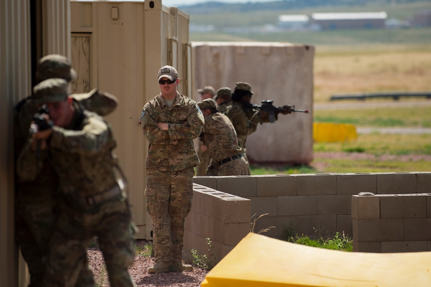 Staff Sgt. Benjamin Davis, 620th Ground Combat Training Squadron formal training instructor, evaluates defenders from Malmstrom Air Force Base's 741st Missile Security Forces Squadron as they enter an urban environment during a tactical response force course at Camp Guernsey, Wyo., July 19, 2017. Defenders who graduate the TRF course will be awarded certification to be members of their squadron's tactical response force team. (U.S. Air Force photo by Staff Sgt. Christopher Ruano)