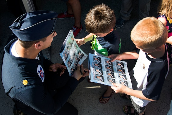 """Maj. Whit Collins, U.S. Air Force Aerial Demonstration Squadron """"Thunderbirds"""" pilot #6 signs autographs for the local and regional community during SkyFest 2017 Air Show and Open House at Fairchild Air Force Base, Washington, July 28, 2017. SkyFest was an opportunity to give the local and regional community a chance to view Airmen and our resources. (U.S. Air Force photo/Senior Airman Janelle Patiño)"""