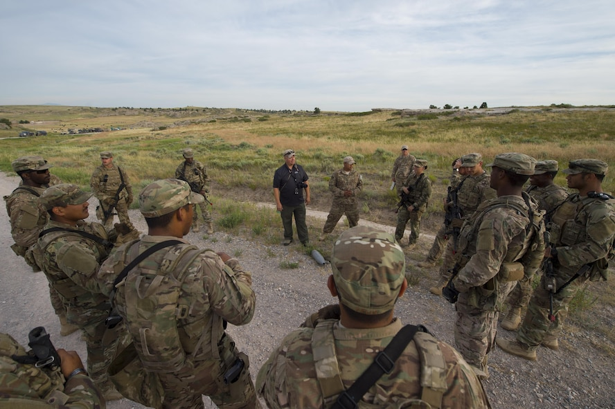 Cayle Harris, 620th Ground Combat Training Squadron counter improvised explosive device instructor, discusses Minot Air Force Base, N.D., 791st Missile Security Forces Squadron Airmen's performance after a counter IED course at Camp Guernsey, Wyo., July 19, 2017. Harris is a retired U.S. Air Force master sergeant and served more than 20 years in the explosive ordinance disposal career field. (U.S. Air Force photo by Staff Sgt. Christopher Ruano)