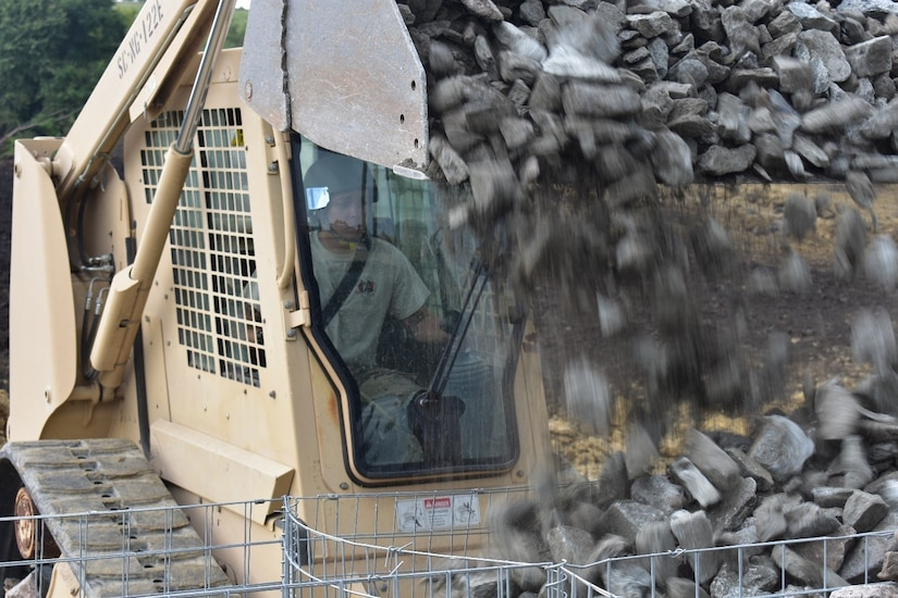Army Spc. Alvin Stevens pours rock into baskets from his loader at the Joint National Training Center in Cincu, Romania, July 15, 2017. Stevens is a South Carolina Army National Guard soldier serving with the 1223rd Engineer Company, 178th Engineer Battalion, deployed to Romania as part of Resolute Castle 17, an operation that builds relationships with the NATO alliance and enhances its capacity for joint training and response to threats within the region. South Carolina Army National Guard photo by Capt. Colin Cutler