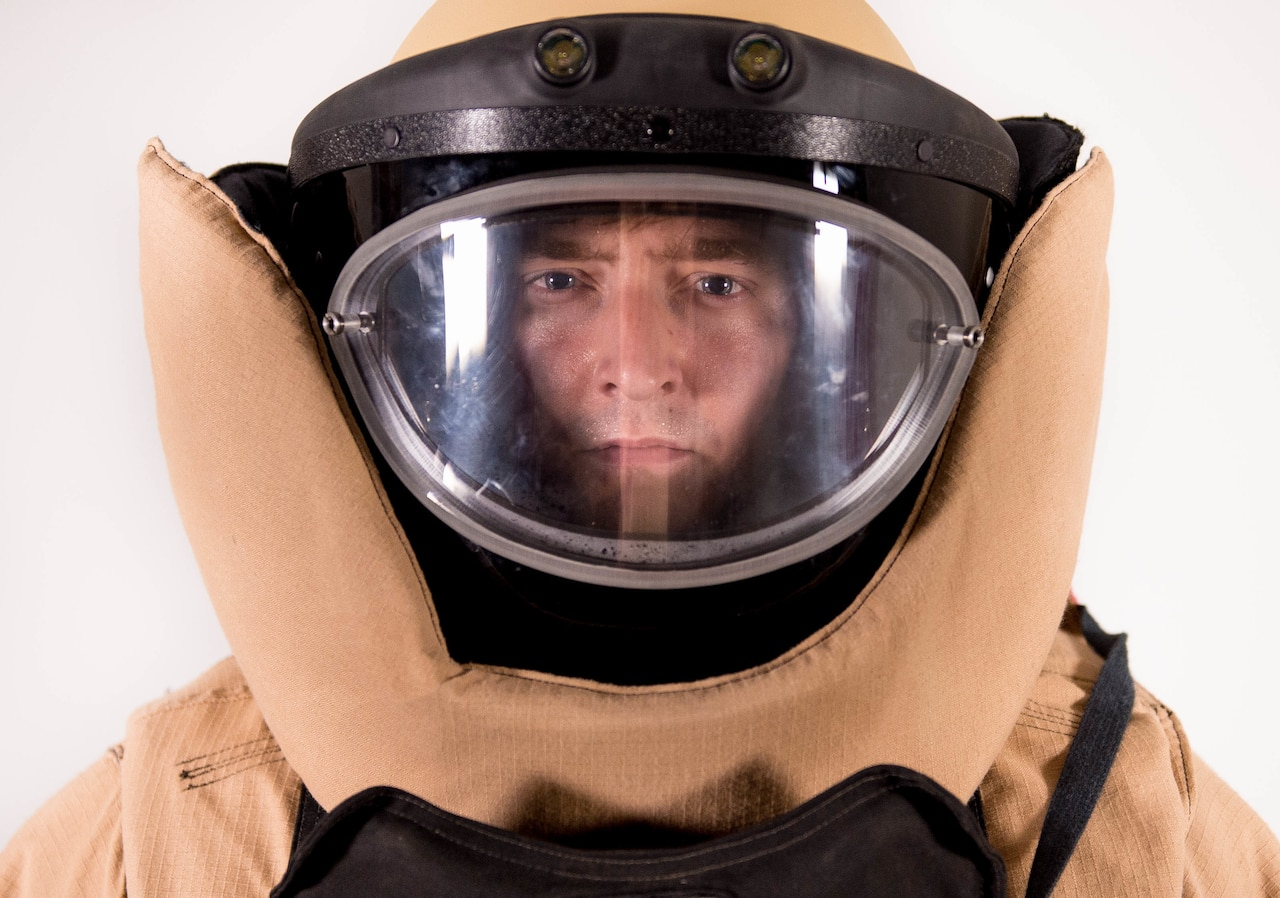 Staff Sgt. Jeffrey Knelange, 56th Civil Engineer Squadron EOD training NCO, stands in his bomb suit at Luke Air Force Base, Ariz., July 10, 2017. Knelange has learned to balance the demands of being an EOD professional while being a key component to the success of the Luke Thunderbolts Hockey team which is a vital part of his comprehensive fitness. (U.S. Air Force photo/Staff Sgt. Jensen Stidham)
