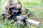 A sniper wearing camouflage and pointing a weapon lays on the grass.