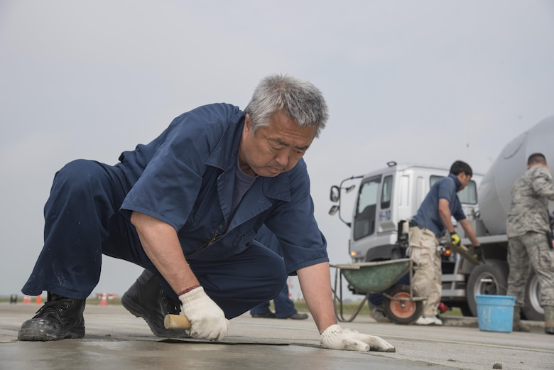 Youichi Yamada, a Japanese contractor, uses a trowel to put finishing touches on newly laid concrete at Misawa Air Base, Japan, May 23, 2017. AFter concrete is laid down, it is smoothed out with a trowel, which pushes heavier rocks down and provides a clean, smooth surface. (U.S. Air Force photo by Airman 1st Class Sadie Colbert)