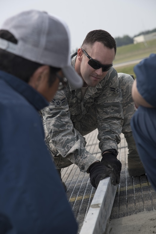 U.S. Air Force Airman 1st Class Samuel Hooper, a 35th Civil Engineer Squadron heavy equipment and pavement technician, works with Yoshinobu Ongasawara, a Japanese contractor, to level concrete on the flight line at Misawa Air Base, Japan, May 23, 2017. The 35th CES worked several weeks with contractors to reconstruct the airfield. (U.S. Air Force photo by Airman 1st Class Sadie Colbert)