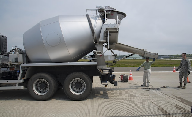 Hiroshi Nakasato, a Japanese contractor, left, readies a concrete truck to fill a spall on the flight line as U.S. Air Force Airman 1st Class Samuel Hooper, a 35th Civil Engineer Squadron heavy equipment and pavement technician, watches, at Misawa Air Base, Japan, May 23, 3017. Concrete is a a mixture of cement, various rocks, water and wood or magnesium. (U.S. Air Force photo by Airman 1st Class Sadie Colbert)
