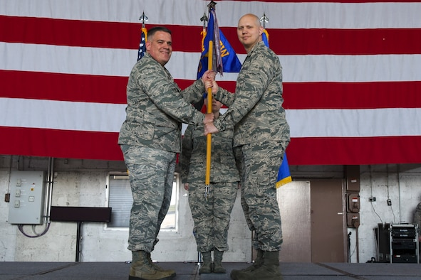 U.S. Air Force Col. Stephen C. Scherzer, 52nd Maintenance Group commander, left, gives the ceremonial guidon to U.S. Air Force Major Christopher R. Pustka, incoming 52nd Maintenance Squadron commander, during the 52nd MXS assumption of command ceremony on Spangdahlem Air Base, Germany, June 1, 2017. (U.S. Air Force photo by Senior Airman Dawn M. Weber)