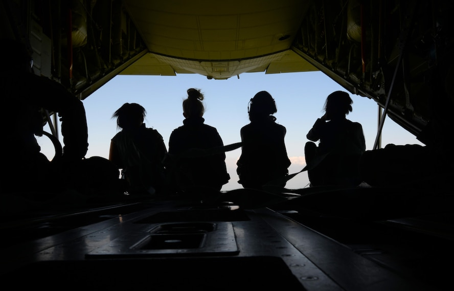 Four spouses sit on the ramp of an MC-130J Commando II during an orientation flight, May 26, 2017, during the 352d Special Operations Wing Spouses Appreciation Day on RAF Mildenhall, England. The flight flew to the White Cliffs of Dover. The orientation flights were provided to give spouses a greater understanding of the mission their Airmen support. (U.S. Air Force photo by Senior Airman Justine Rho)