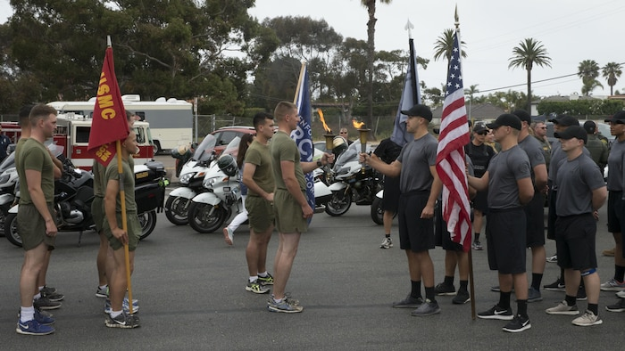 U.S. Marines with Security and Emergency  Services Battalion, Marine Corps Base Camp Pendleton, Marine Corps Installations–West, hands off the torch to Orange County Sheriff Department Special Olympics torch from runners of the Oceanside Police Department at San Clemente, Calif., May 31st, 2017. More than 30 Marines from the SES and  the installation Provost Marshal Office participated in the 2017 Law Enforcement Torch Run in support of the Special Olympics. The Marines received the torch from runners with the Oceanside Police Department at the Camp Pendleton Main Gate, Calif., May 31st, 2017. SES Bn. Marines then relayed the torch and ran it 17 miles to San Clemente.