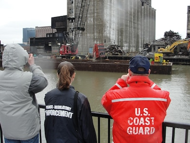 Corps of Engineers Regulatory observe the removal of grain silo debris from the Buffalo River.