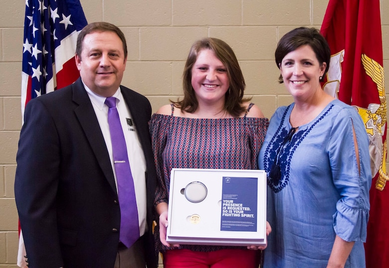 """Gracyn LeSueur (center) poses for a photo with her father, Kevin LeSueur (left), and mother Michelle LeSueur (right) after being presented with the Semper Fidelis All-American award at Northview High School, May 18, 2017. """"I want to thank my mom and dad for never giving up on me, and pushing me to be what I am today,"""" LaSueur said. LaSueur will attend the Battles Won Academy this summer in Washington D.C., where she will be given the opportunity to network with and hear from an elite circle of leaders from all walks of life, who like her, have fought and won their own battles. (U.S. Marine Corps photo by Cpl. Krista James/Released)"""