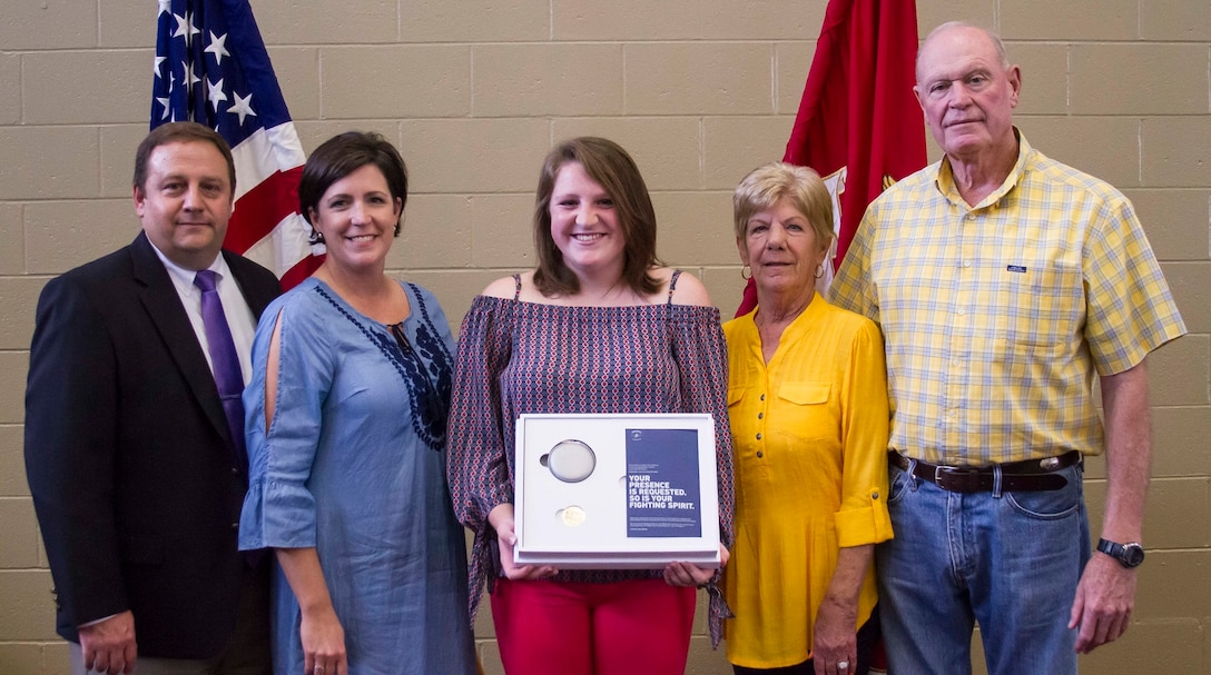 Gracyn LeSueur (center) poses for a photo with her parents, Kevin and Michelle LaSueur (left), and her grandparents, Grace and Doug Bennefield (right), after being presented with the Semper Fidelis All-American award at Northview High School, May 18, 2017. LaSueur was one of 100 students who will attend the Battles Won Academy this summer in Washington D.C., where she will be given the opportunity to network with and hear from an elite circle of leaders from all walks of life, who like her, have fought and won their own battles. (U.S. Marine Corps photo by Cpl. Krista James/Released)
