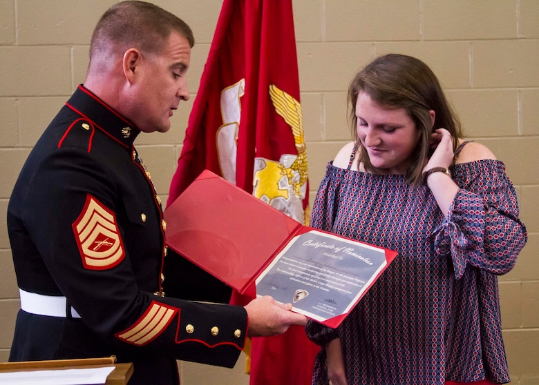 Gunnery Sgt. Matthew Hoyle, the station commander for Recruiting Substation Dothan, Alabama, presents a certificate to Gracyn LaSueur, who was chosen as one of a 100 Semper Fidelis All-Americans, at Northview High School, May 18, 2017. The Marine Corps wanted to find young student athletes who encompass the core values of honor, courage and commitment. These are the Semper Fidelis All-Americans. These students have faced life's battles with the conviction and determination to succeed. They embody the same fighting spirit that Marines stand for by taking on their own challenges and succeeding academically, while excelling in athletics and making their community a better place. (U.S. Marine Corps photo by Cpl. Krista James/Released)