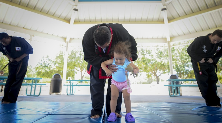 Amado Garcia, a Kuk Sool Won instructor, bows with his daughter after completing a demonstration at the Asian American and Pacific Islander Cultural Day event at Hurlburt Field, Fla., May 25, 2017. Kuk Sool Won is a martial art system that was founded in 1961. The event included the demonstration, free food and a hula demonstration. (U.S. Air Force photo by Airman 1st Class Dennis Spain )
