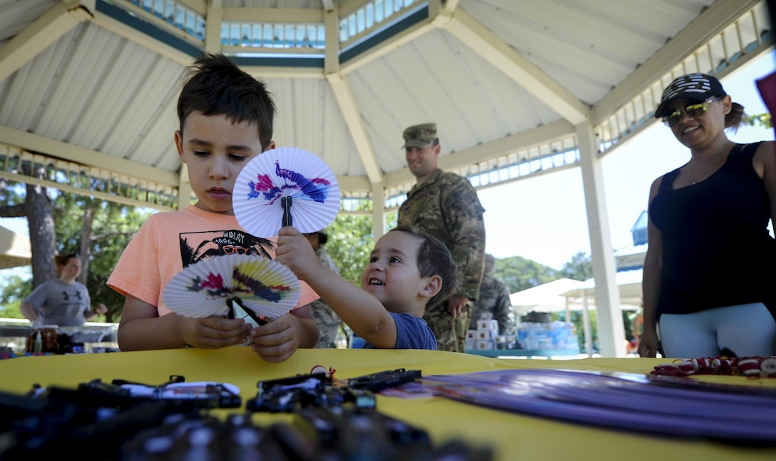 Damien and Daniel Wright, sons of Capt. Tim Wright, a gunship electronic warfare officer with the 4th Special Operations Squadron, play with fixed fans at the Asian American and Pacific Islander Cultural Day event at Hurlburt Field, Fla., May 25, 2017. The event included free food, a Kuk Sool Won demonstration and a hula demonstration. (U.S. Air Force photo by Airman 1st Class Dennis Spain)