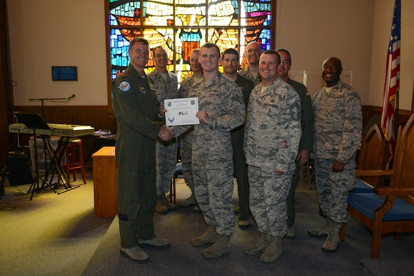 "U.S. Air Force Staff Sgt. Jason Black, 47th Flying Training Wing Chapel plans and programs NCO in charge, (center), accepts the ""XLer of the Week"" award from Col. Thomas Shank, 47th Flying Training Wing commander (left), and Chief Master Sgt. Allen Turk, 47th Operations Support Squadron superintendent (right), on Laughlin Air Force Base, Texas, May 25, 2017. The XLer is a weekly award chosen by wing leadership and is presented to those who consistently make outstanding contributions to their unit and installation. (U.S. Air Force photo/Airman 1st Class Benjamin N. Valmoja)"