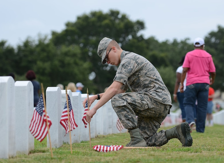 Airman Basic Charlie Evans, 335th Training Squadron student, places a U.S. flag in front of a tomb stone at Biloxi National Cemetery in recognition of Memorial Day, May 27, 2017, in Biloxi, Miss. Local veterans, family members and Keesler AFB personnel participated in the event to honor and remember the lives of fallen heroes of the U.S. military. (U.S. Air Force photo by Andrew Whitman)