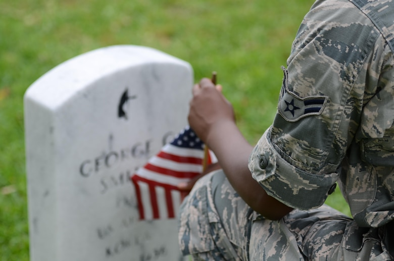 Airman 1st Class Kymyenna Mitchell, 335th Training Squadron student, places a U.S. flag in front of a tomb stone at Biloxi National Cemetery in recognition of Memorial Day, May 27, 2017, in Biloxi, Miss. Local veterans, family members and Keesler AFB personnel participated in the event to honor and remember the lives of fallen heroes of the U.S. military. (U.S. Air Force photo by Andrew Whitman)