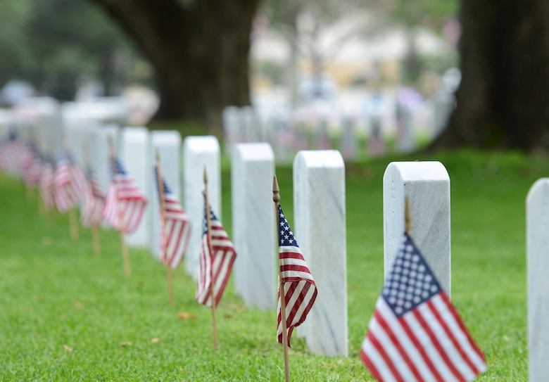 U.S. flags stand in front of tomb stones at Biloxi National Cemetery in recognition of Memorial Day, May 27, 2017, in Biloxi, Miss. Local veterans, family members and Keesler AFB personnel participated in the event to honor and remember the lives of fallen heroes of the U.S. military. (U.S. Air Force photo by Andrew Whitman)