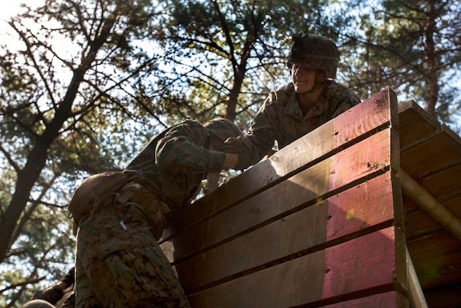 A Marine helps a team member up a high wall obstacle at the Leadership Reaction Course at Camp Mujuk, South Korea, May 29, 2017. Marine Corps photo by Cpl. David A. Diggs
