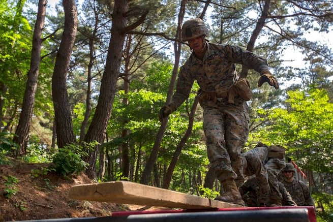 Marines and sailors walk across a wooden plank as part of the Leadership Reaction Course at Camp Mujuk, South Korea, May 29, 2017. Marine Corps photo by Cpl. David A. Diggs