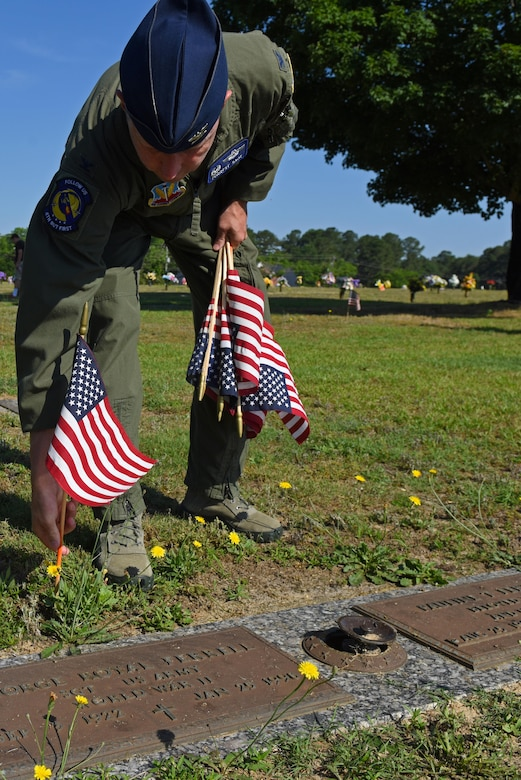 Col. Christopher Sage, 4th Fighter Wing commander,  places a flag behind a headstone of a veteran, May 27, 2017, at Wayne Memorial Park in Dudley, North Carolina. Sage spoke at a breakfast hosted by the Wayne County Veterans & Patriots Coalition then assisted in distributing flags on veterans' final resting places. (U.S. Air Force photo by Senior Airman Ashley Maldonado-Suarez)