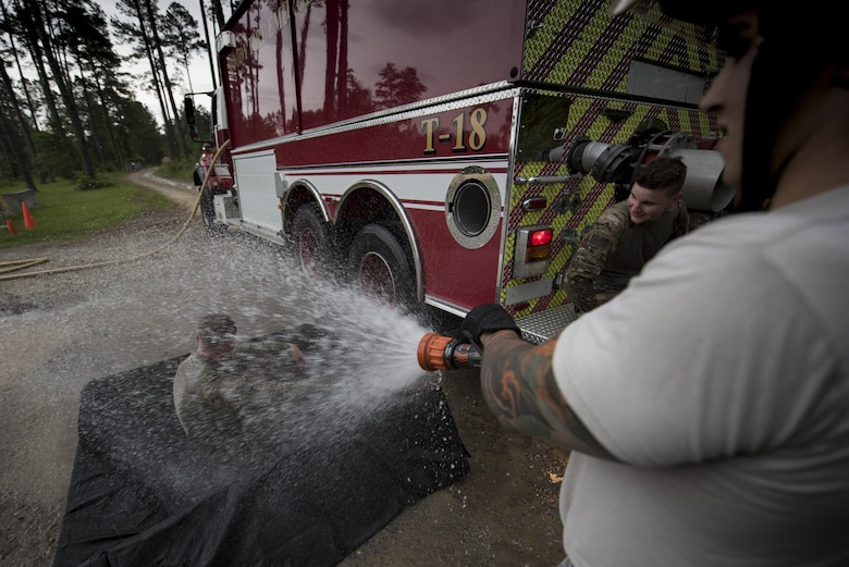 Senior Airman Frank Boniello, 23d Civil Engineer Squadron firefighter performs an initial decontamination of Senior Airman Jonah Phillips, 822d Base Defense Squadron fireteam member during a simulated explosives and hazardous material scenario, May 24, 2017, at Moody Air Force Base, Ga. The exercise simulated initial responses from first responders who then contacted other appropriate units after assessing the potential threat while also assisting the simulated victims of hazardous materials. (U.S. Air Force photo by Airman 1st Class Daniel Snider)