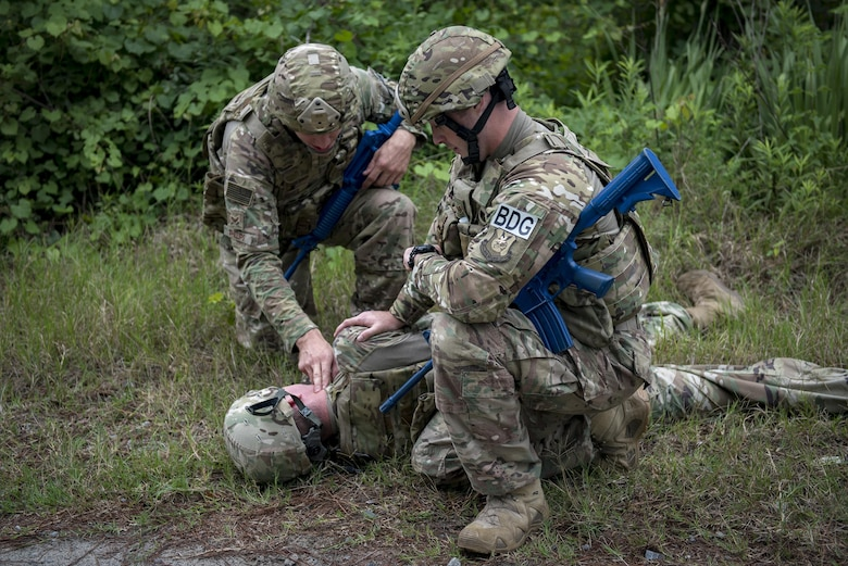 Senior Airman Jonah Phillips, 822d Base Defense Squadron fireteam member and Staff Sgt. Joshua Basinger, 822d BDS fireteam leader, check the vitals of an unconscious team member during a simulated explosives and hazardous material scenario, May 24, 2017, at Moody Air Force Base, Ga. The exercise was designed to simulate initial responses from first responders. Once on scene, they contacted other appropriate units after assessing the potential threat while also assisting the simulated victims of hazardous materials. (U.S. Air Force photo by Airman 1st Class Daniel Snider)