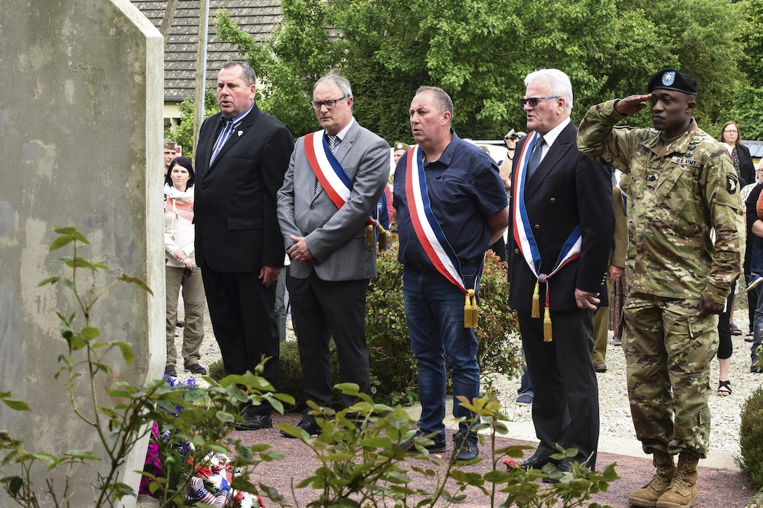 A soldier salutes while attending a ceremony with French citizens and fellow U.S. paratroopers