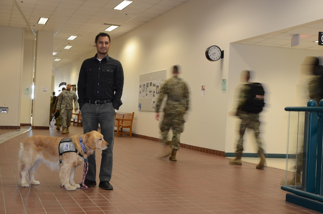 Cadence, Rod Foliente's service dog, and Rod Foliente, an Intermediate Photojournalism Course instructor, stands in the second floor hallway of the Defense Information School on Fort Meade May 15, 2017 as students go to class. Cadence has become a welcome addition to the DINFOS family since Foliente brought Cadence to DINFOS on April 4, 2017.