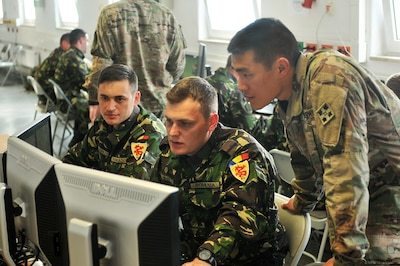 From left, Romanian army 1st Lt. Sergio Gligor, an operations officer, and 2nd Lt. Andrei Ma, a battle captain, both with the 811th Infantry Battalion, and U.S. Army 1st Lt. Jeff Yao, a military intelligence officer with the 3rd Armored Brigade Combat Team, 4th Infantry Division, track a counterattack in a simulated fight against a conventional force during a command-post exercise conducted at Grafenwoehr Training Area, Germany, May 16, 2017. Army photo by Capt. Scott Walters