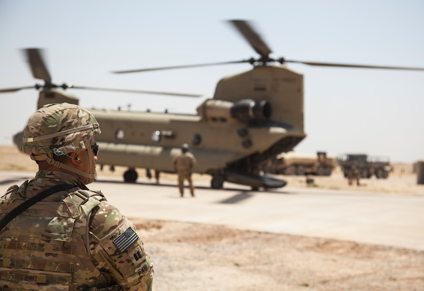 A U.S. soldier deployed in support of Combined Joint Task Force Operation Inherent Resolve waits while a CH-47 Chinook is refueled at Qayyarah West Airfield, Iraq, May 29, 2017. Army photo by Cpl. Rachel Diehm