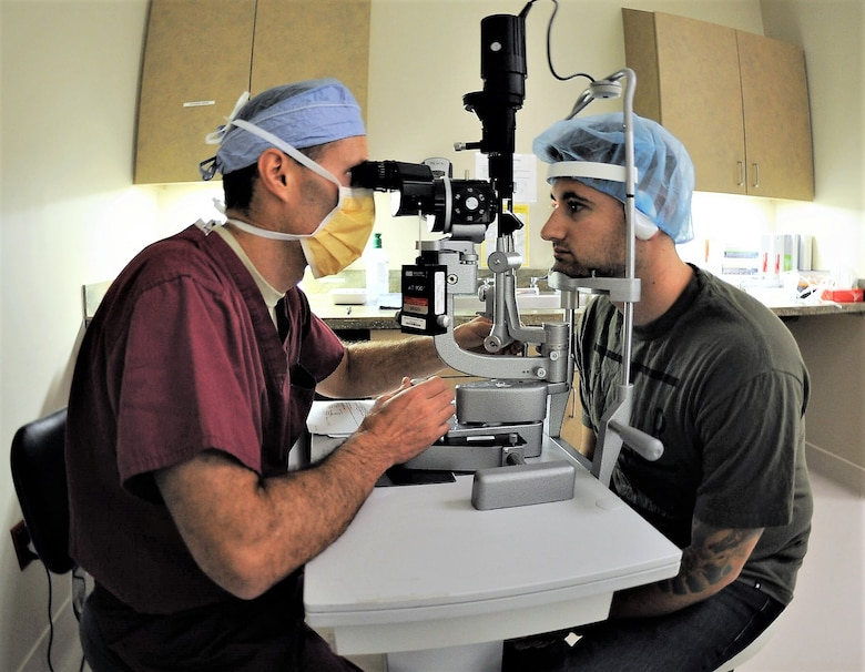 Maj. Williams Gensheimer (left), 779th Medical Group's Warfighter Eye Center chief, inspects the corneas of Staff Sgt. John Scacca, 633rd Medical Group, Joint Base Langley-Eustis, Va., before performing corneal refractive surgery May 17, 2017 at Joint Base Andrews, Md. PRK, LASIK and other types of laser eye surgery involve using an excimer laser to re-shape the cornea, which allows for light to enter the eye that is properly focused onto the retina for improved vision. (U.S. Air Force photo by Joe Yanik)