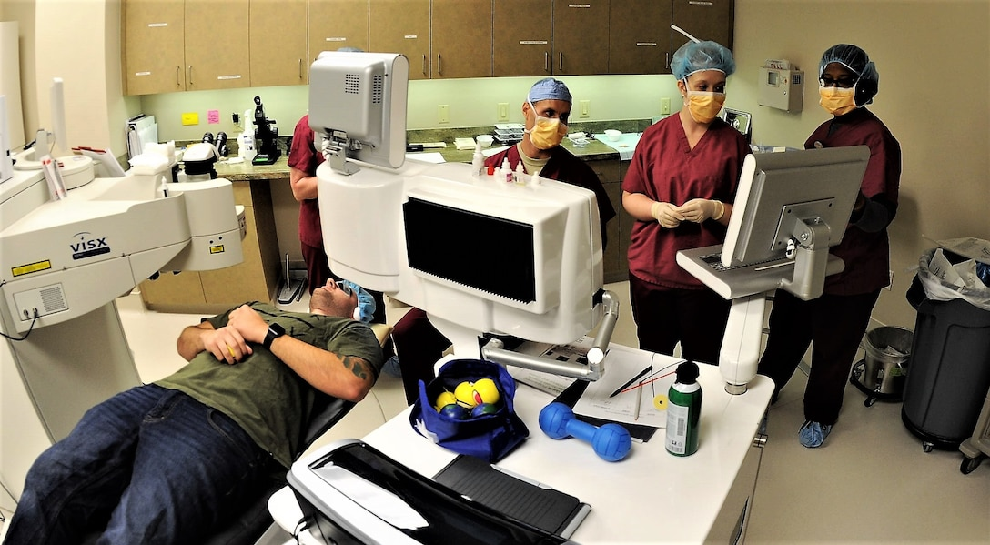 Staff Sgt. John Scacca, 633rd Medical Group, Joint Base Langley-Eustis (lying down), waits as Dr. Williams Gensheimer (sitting), 779th Medical Group's Warfighter Eye Center chief, and his staff of refractive technicians verify patient data before beginning corneal refractive surgery May 17, 2017 at Joint Base Andrews, Md. JBA's Warfighter Eye Center is one of only six of the Air Force's corneal refractive surgery centers. (U.S. Air Force photo by Joe Yanik)