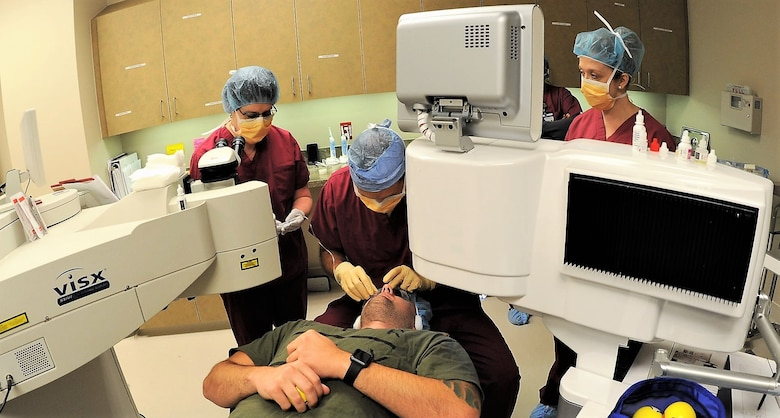 Dr. William Gensheimer (left), 779th Medical Group's Warfighter Eye Center chief, places a lid speculum over one of a patient's eyes May 17, 2017 at Joint Base Andrews, Md. It serves to force the patient's eyelids to remain open while the laser re-shapes the cornea. (U.S. Air Force photo by Joe Yanik)
