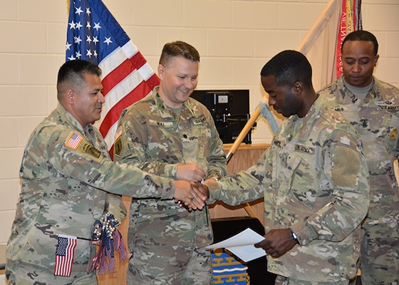 Defense Logistics Agency Aviation Army Maj.  Alex Shimabukuro shakes the hand of Army Private 1st Class Didier Martel Florestal, a native of Haiti, during his naturalization ceremony May 30, 2017 at Fort Lee, Virginia's Soldier Support Center. Also pictured:  Army Lt. Col. Brian Neill, commander, 266th Quartermaster Battalion, center, and 266th Battalion Command Sergeant Major James Holmes, right.